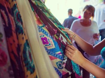 Woman choosing clothes at flea market
